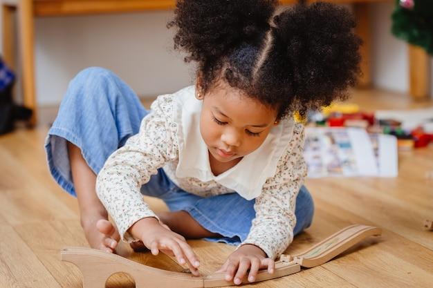 Klein schattig kind meisje genieten van houten puzzel spelen op de houten vloer thuis in de woonkamer.