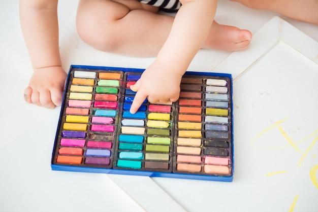 Klein schattig kind met creativiteit tekent met kleurpotloden thuis op een vel wit papier. het concept van de vroege ontwikkeling van creativiteit door kinderen