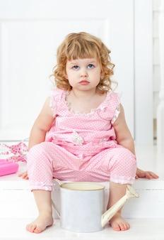 Klein schattig krullend meisje in een roze jurk met stippen zittend op de witte veranda provence stijl