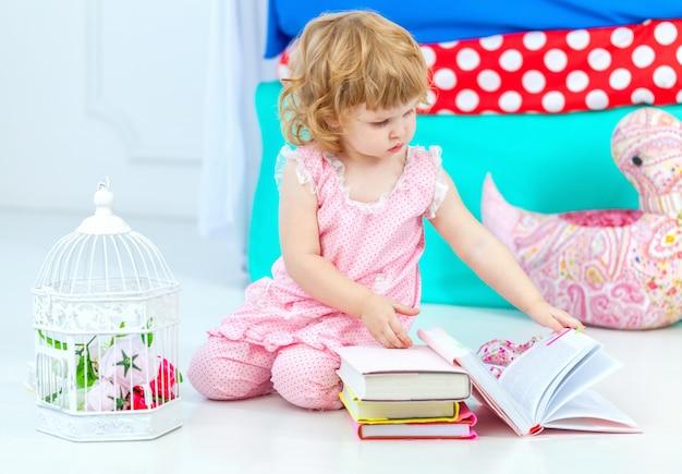 Klein schattig krullend meisje in roze pyjama kijken naar het boek zittend op de vloer in de kinderkamer,