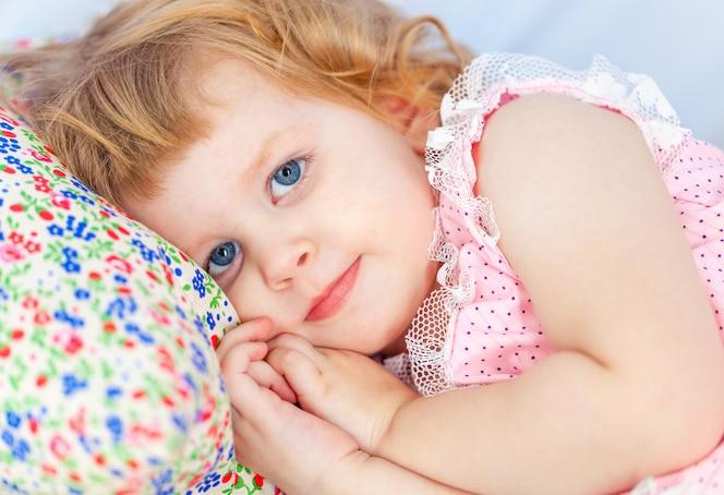 Klein schattig krullend meisje ligt in een babybed en een hand onder haar wang.