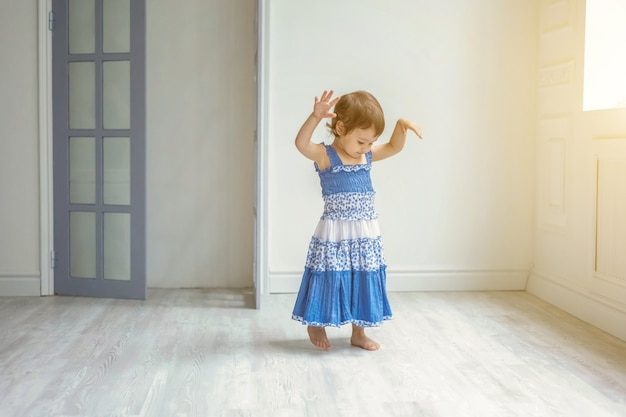 Klein schattig lief lachend meisje in blauwe jurk dansen in fel lichte woonkamer thuis en lachen. jeugd, kleuterschool, jeugd, ontspannen concept