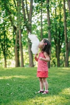 Klein schattig meisje 3-4 suikerspin eten in zonnig park, tussen hoge bomen op groen gras. verticaal