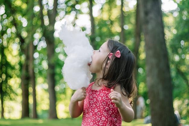 Klein schattig meisje 3-4 suikerspin eten in zonnig park, tussen hoge bomen op groen gras