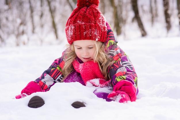 Klein schattig meisje begraven in de sneeuw