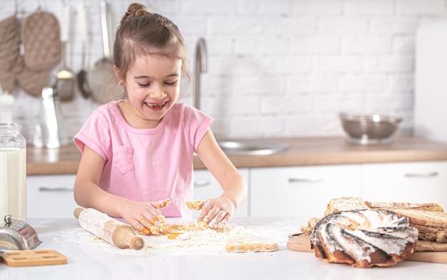 Klein schattig meisje bereidt deeg voor thuis bakken op de achtergrond van het interieur van de keuken.