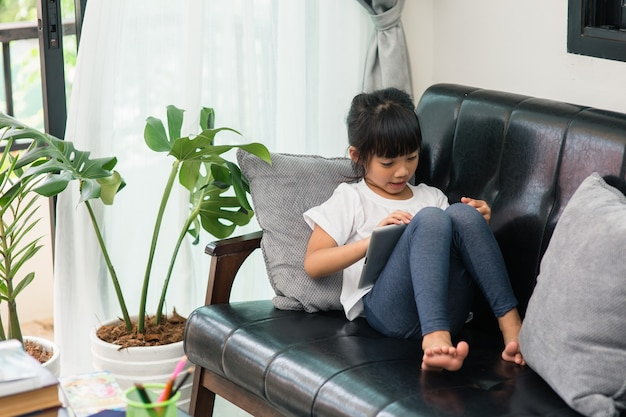 Klein schattig meisje dat spelletjes speelt op een tablet en tekenfilms kijkt