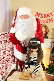 Klein schattig meisje dat thuis een brief schrijft aan de kerstman in de buurt van de kerstboom