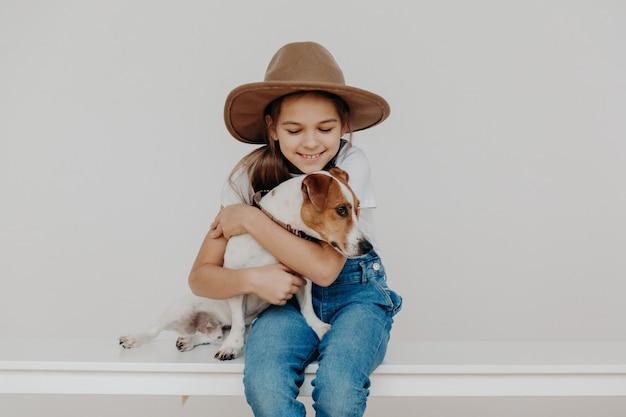 Klein schattig meisje draagt modieuze hoed en denim overall, omarmt favoriete hond met liefde