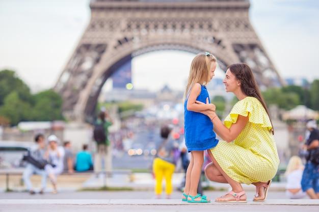 Klein schattig meisje en haar jonge moeder in parijs in de buurt van de eiffeltoren tijdens de zomervakantie