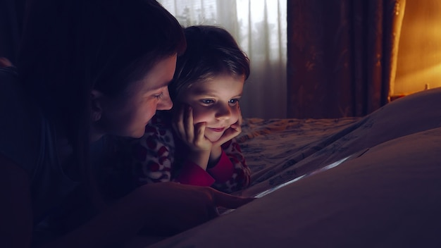 Klein schattig meisje en haar moeder kijken naar tablet