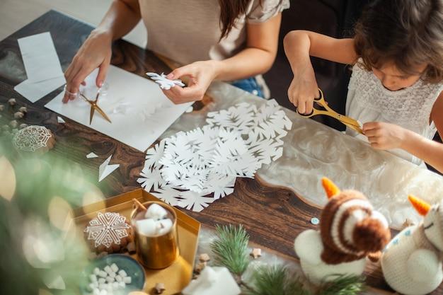Klein schattig meisje en jonge mooie vrouw knippen sneeuwvlokken uit wit papier. peperkoek en cacao met marshmallows. het concept van voorbereiding op het nieuwe jaar en kerstmis.