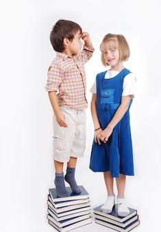 Klein schattig meisje en jongen met veel boeken geïsoleerd