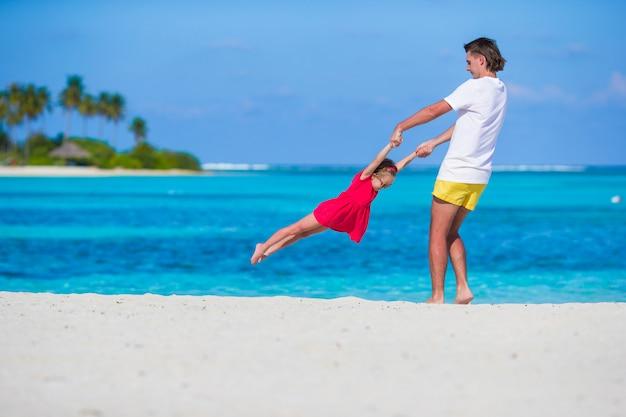 Klein schattig meisje en papa tijdens tropische strandvakantie