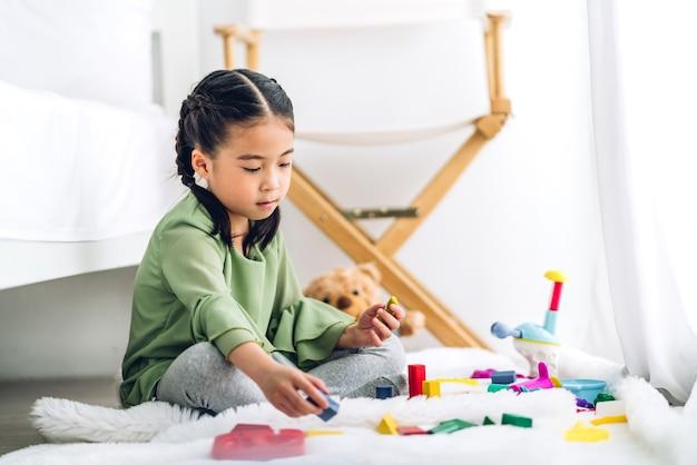 Klein schattig meisje geniet tijdens het spelen van houten blokken speelgoed op tafel thuis