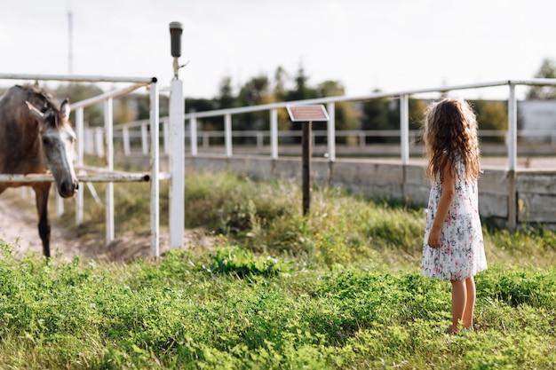 Klein schattig meisje geniet van wandelen op de boerderij en paard kijken.