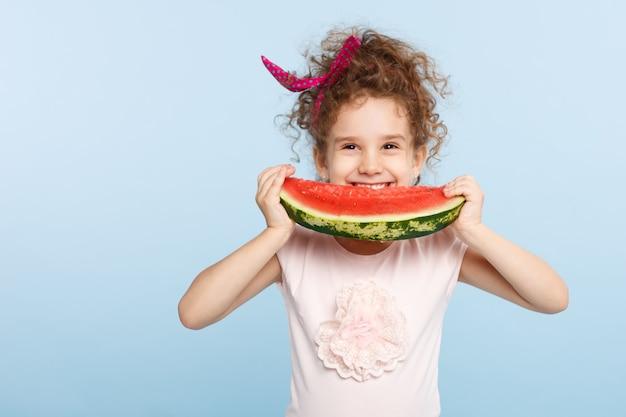 Klein schattig meisje glimlachend en watermeloen eten