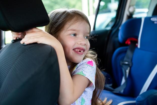 Klein schattig meisje glimlachend in de autostoel