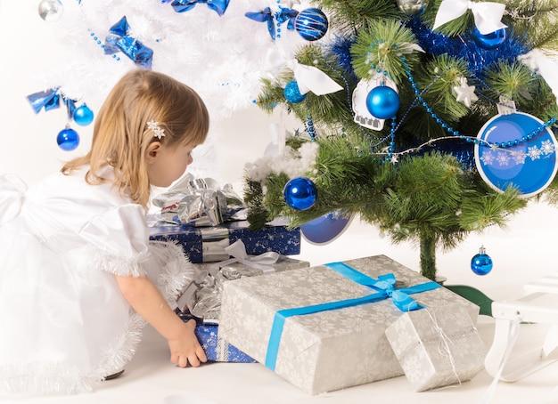 Klein schattig meisje heeft een nieuwjaarsgeschenk in haar handen en kijkt naar een kerstboom versierd met blauw speelgoed op een witte achtergrond.