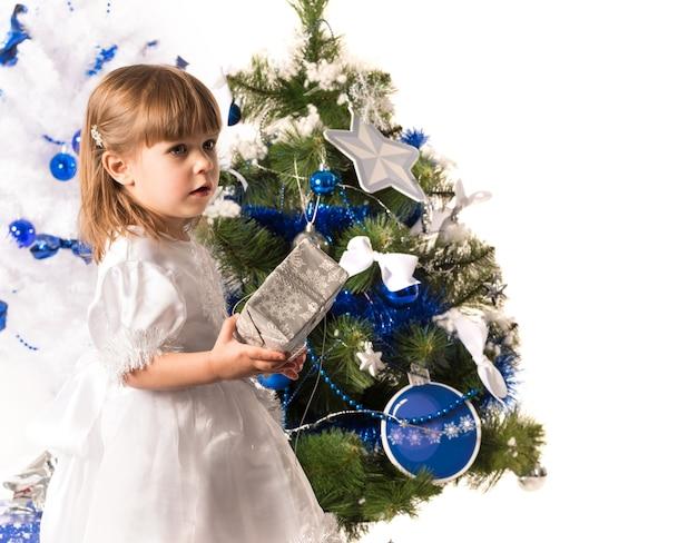 Klein schattig meisje heeft een nieuwjaarsgeschenk in haar handen en kijkt naar een kerstboom versierd
