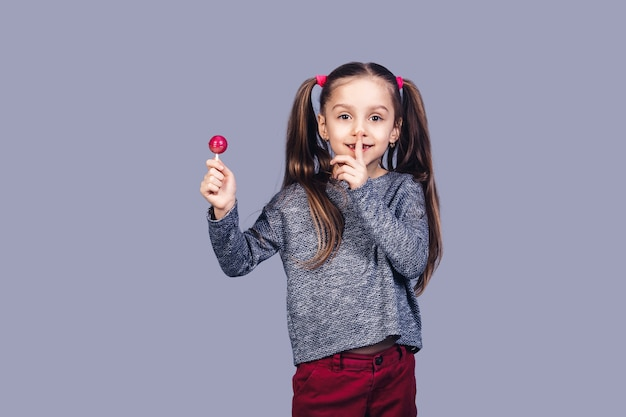 Klein schattig meisje houdt rode lolly in de hand en toont shh. geïsoleerd op grijs oppervlak