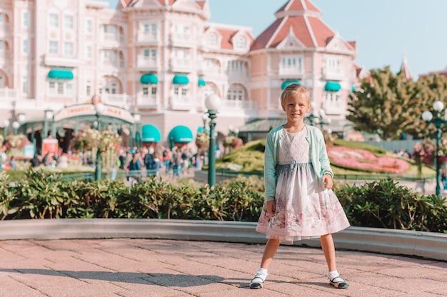 Klein schattig meisje in assepoester jurk bij sprookjesachtige disneyland park