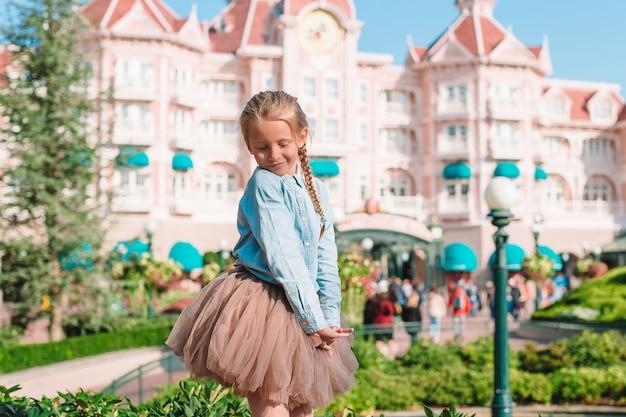 Klein schattig meisje in assepoesterjurk in sprookjesachtig disneyland-park