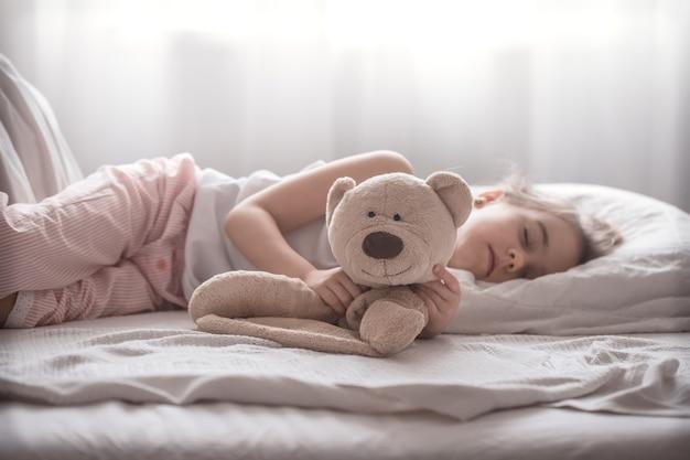 Klein schattig meisje in bed met speelgoed