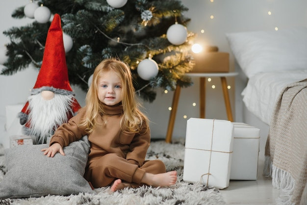 Klein schattig meisje in de buurt van de kerstboom