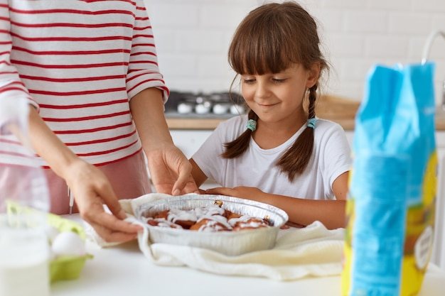 Klein schattig meisje in de keuken kijken naar een lekker bakdessert op tafel, poserend in de buurt van gezichtsloze moeder die gebak op tafel legt, vrouwelijk kind met tevreden gezichtsuitdrukking.