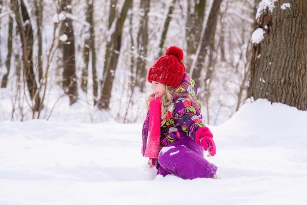 Klein schattig meisje in de sneeuw