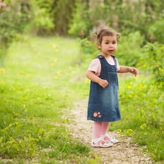 Klein schattig meisje in de tuin, loopt op het pad
