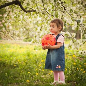 Klein schattig meisje in de tuin, speelt met bal
