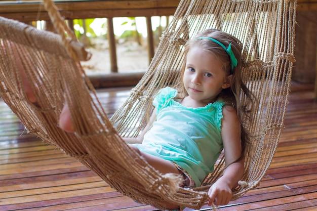 Klein schattig meisje in een hangmat op het terras van haar huis
