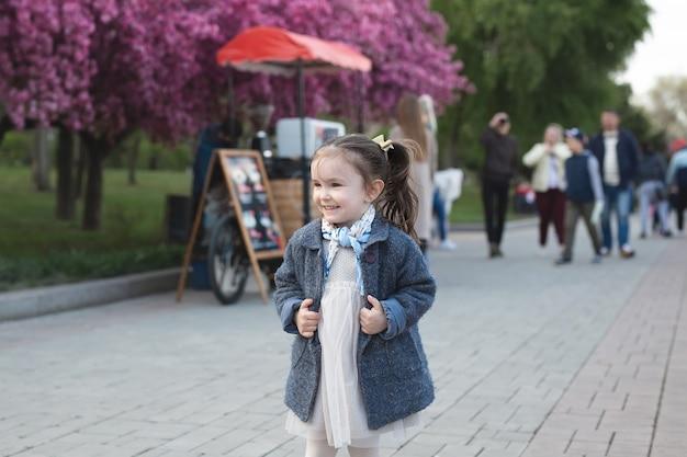 Klein schattig meisje in een jas loopt in het park