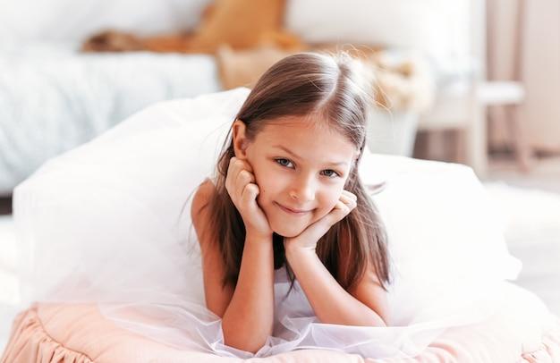 Klein schattig meisje in een mooie witte jurk rusten in een lichte kinderkamer