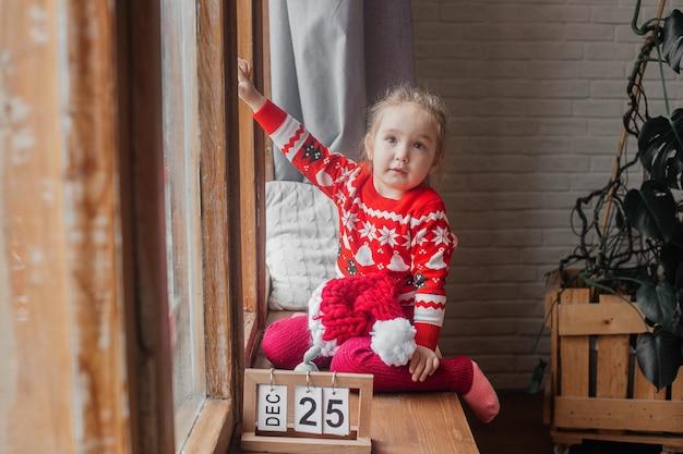 Klein schattig meisje in een new year's trui glimlacht zittend aan het raam.