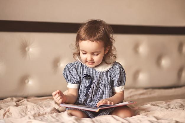 Klein schattig meisje in een retro jurk lezen van een boek.