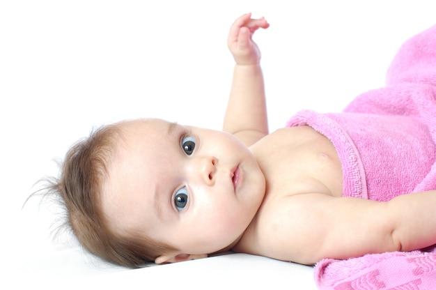 Klein schattig meisje in een roze handdoek