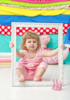 Klein schattig meisje in een roze pak zittend op de vloer en lachend over houten wit frame.