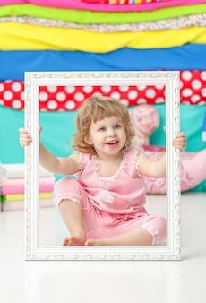 Klein schattig meisje in een roze pak zittend op de vloer en lachend over houten wit frame