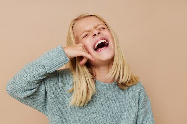Klein schattig meisje in een trui grimassen bijgesneden weergave