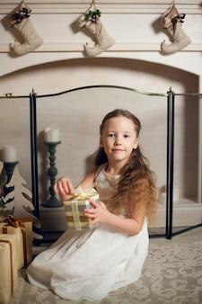Klein schattig meisje in jurk zitten in de buurt van kerstboom en geschenken te houden. nieuwjaar.