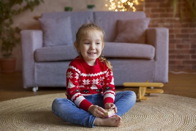 Klein schattig meisje in rode kerst trui spelen in de woonkamer met geschenken