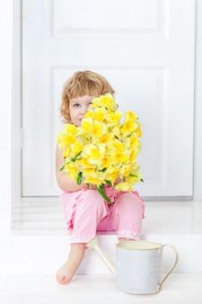 Klein schattig meisje in roze jurk zittend op een witte veranda en verbergt haar gezicht achter een boeket bloemen,