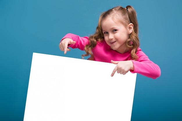 Klein schattig meisje in roze shirt met aap en blauwe broek houden lege blanco plakkaat