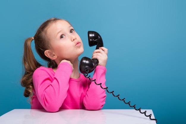 Klein schattig meisje in roze shirt met aap en blauwe broek praat via de telefoon
