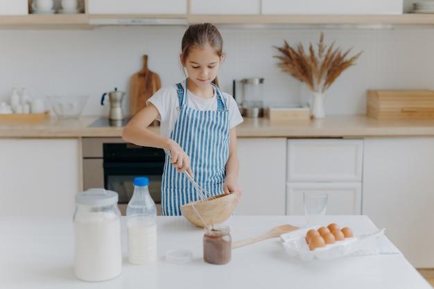 Klein schattig meisje in schort, mengt ingrediënten, zwaait met klopper, gebruikt eieren, melk, bloem, probeert nieuw recept, staat tegen keuken