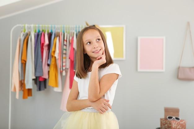 Klein schattig meisje kiest kleding in kleedkamer