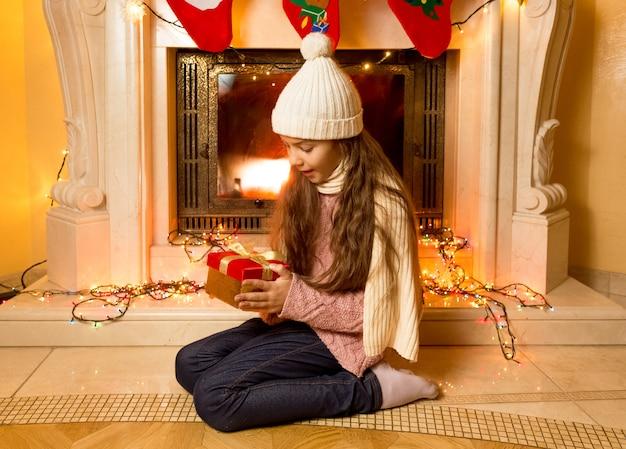 Klein schattig meisje kijkt naar kerstcadeau bij open haard